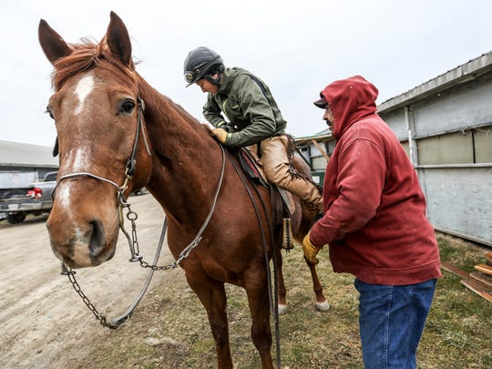 Horse Trainer James Jackson, 72, of Highland Twp helps jockey Melissa Zajac, 31, mount a horse to exercise it at the closed Hazel Park Raceway on Wednesday, April 11, 2018. Zajac, was discovered by Jackson and plans to continue racing horses with him in Cincinnati, Ohio.