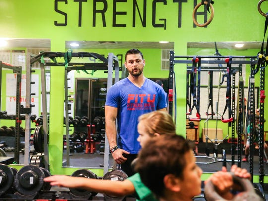 Matt Cutrer watches students perform an exercise during a youth training camp Wednesday, July 18, 2018, at Fitness United.
