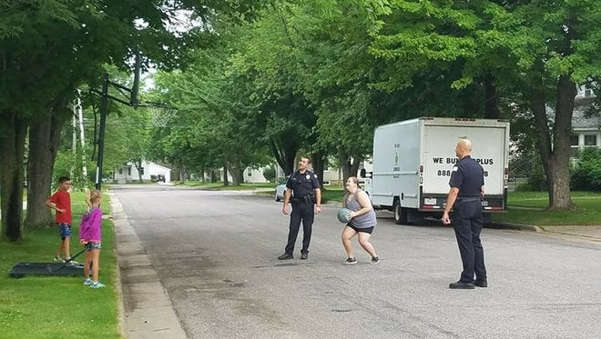"""Wisconsin Rapids Police Officer Dustin Gessert, left, and Lt. Brian Krzykowski, play basketball with two Wisconsin Rapids children and their babysitter Thursday after a """"cranky"""" neighbor lady called in a complaint about the children."""