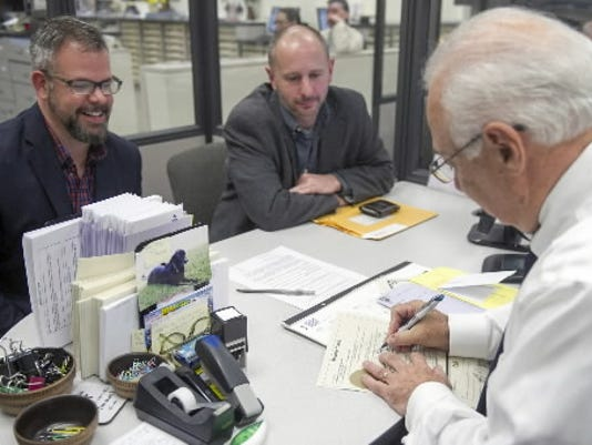 Bradley C. Jacobs, right, signs the first same-sex marriage license in York County at the York County Judicial Center Wednesday May 21, 2014. Will Guntrum, left, and David Satterlee are seated across from him. Paul Kuehnel - Daily Record/Sunday News
