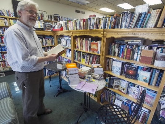 Byron Borger stands with a new book Sept. 10 in Hearts & Minds in Dallastown. Getting to know your independent bookstores can offer bargains in the long run. (DAILY RECORD/SUNDAY NEWS -- PAUL KUEHNEL)