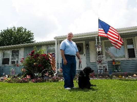 Author Kevin Turnbaugh, who lost his sight to an eye disease, stands with his guide dog, Jodi, outside his home in New Oxford. (FOR THE DAILY RECORD/SUNDAY NEWS -- CLARE BECKER)
