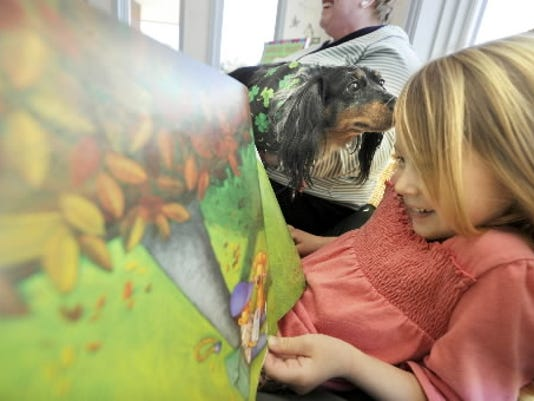 Caylyn Ballou, 5, gets her hair sniffed by Tibby as she reads aloud to the dog in March during the Tales for Tails therapy dog program at Glatfelter Memorial Library in Spring Grove. (YORK DAILY RECORD/SUNDAY NEWS -- JASON PLOTKIN)