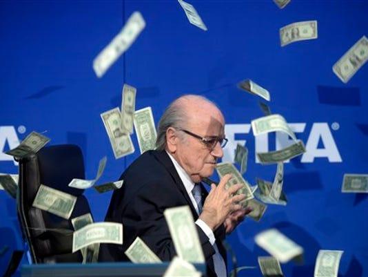 """El presidente de la FIFA Joseph Blatter es bañado por una lluvia de billetes falsos que le tiró un comediante británico durante una conferencia de prensa en Zúrich el 20 de junio del 2015.""""Esto es por Corea del Norte 2026"""", le dijo Simon Brodkin, mientras ponía billetes frente a Blatter, aludiendo a una ficticia selección de Corea del Norte como sede de la Copa Mundial del 2026. """"Grande Sepp. Gracias. Te entregué todo, como hablamos. Gracias. Me complace hacer negocios contigo"""", agregó Brodkin mientras lo sacaban del recinto. (Ennio Leanza/Keystone via AP)"""
