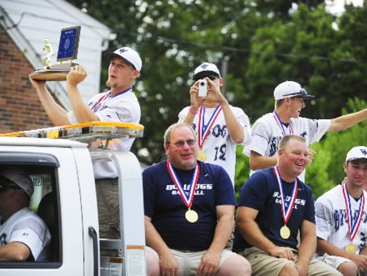 West York baseball players celebrated their first PIAA championship with a parade last July. Jesse Bortner holds up the team's PIAA Class AAA state championship trophy as he, teammates and staff ride on a flatbed truck during last year's parade. (DAILY RECORD/SUNDAY NEWS - CHRIS DUNN)