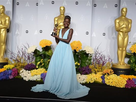 "Lupita Nyong'o poses in the press room with the award for best actress in a supporting role for ""12 Years"