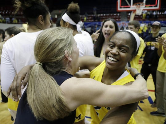 Michigan head coach Kim Barnes Arico hugs guard Siera Thompson after their 89-79 win in triple-overtime in the WNIT championship game against Georgia Tech.