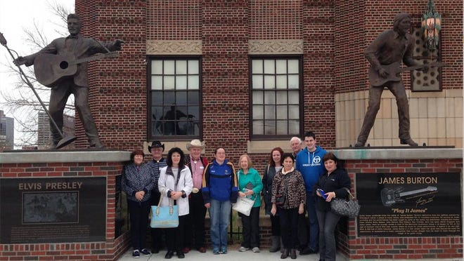 Johnny Wessler leads a visiting group from Ireland through Shreveport on a historical music tour. The guests pose at Municipal Auditorium's Elvis Presley and James Burton statues.
