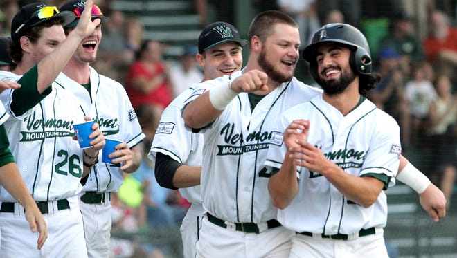 Vermont Mountaineers' Jack Parenty, far right, celebrates with teammates after scoring a run in the first inning of Game 2 of the NECBL championship series Monday night in Montpelier.