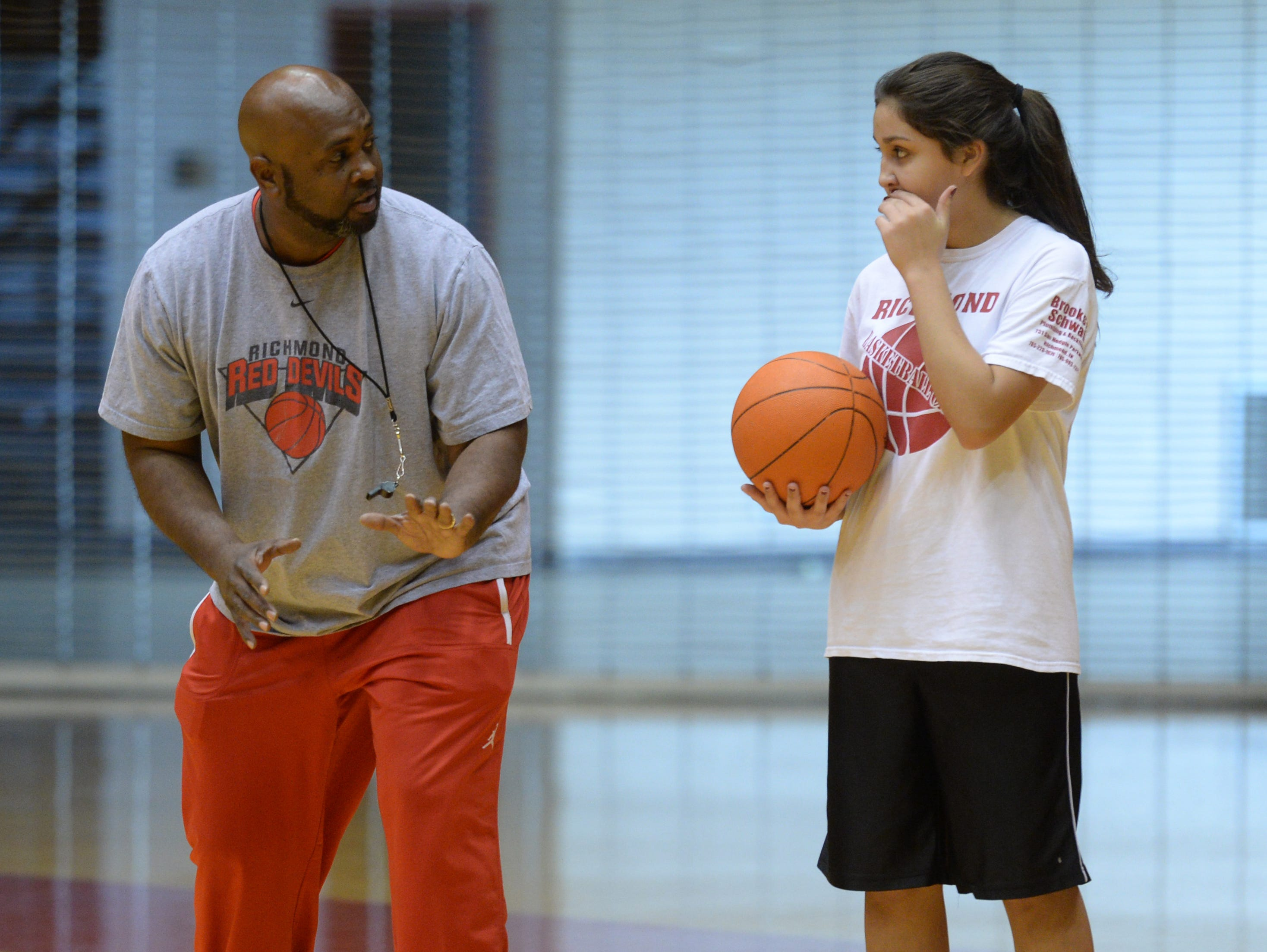 Richmond High School basketball coach Rick Wedlow gives a tip to a participant during a basktball camp for young athletes Saturday, Nov. 7, 2015 in Richmond.