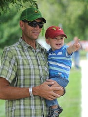 Jason Welty and his son, Boone, 1, of Wautoma, wait for Betsy Welty to go by in the Race The Lake bike race at Lakeside Park in Fond du Lac on August 17, 2014.