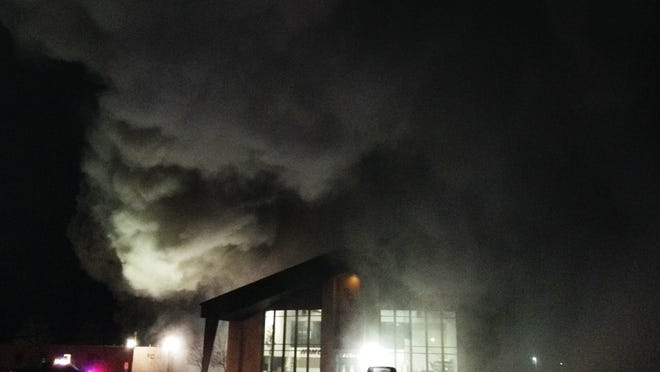 Smoke billows from a maintenance building west of the gym (lighted building in foreground) Saturday at Rite of Passage-Silver State Academy.
