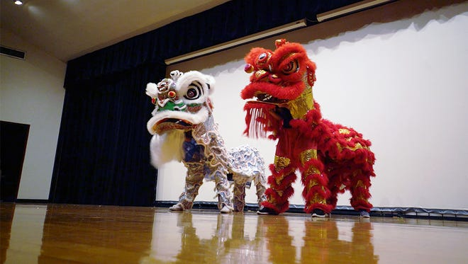 Students perform the lion dance at the Mid-Autumn Festival with  Amber Chu and Maggie Ng as the silver dragon and Michael Cho and Anthony Tieu as the red dragon.
