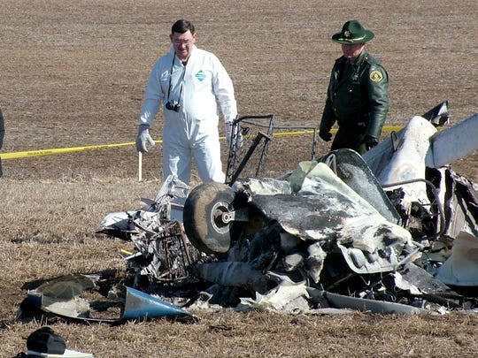 Marty Fisher, sheriff of Fayette County, Iowa, views the crash site of the Piper Cherokee that carried 8-year-old Caryn Stewart and some of her family members. It was her first flight.