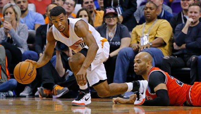 Phoenix Suns guard Ronnie Price (14) and Chicago Bulls forward Taj Gibson (22) fight for a loose ball in second half of their NBA game Wednesday, Nov. 18, 2015 in Phoenix.