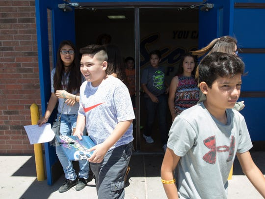 Students from Picacho Middle School rush out of the gym as the school is released in May 2017.
