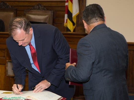 Judge Daniel Powell signs the register for the clerk of the court on Friday, Sept. 1. More than 250 people attended the swearing in for the new judge in the Circuit Court for Somerset County.