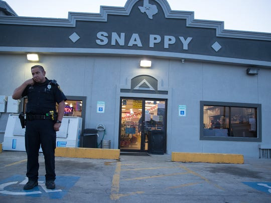 A police officer stands in front of a snappy's after