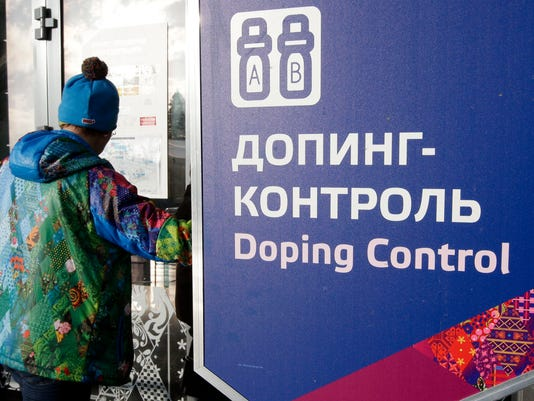FILE - In this Feb. 21, 2014, file photo, a man walks past a sign reading doping control, at the Laura biathlon and cross-country ski center, at the 2014 Winter Olympics in Krasnaya Polyana, Russia. (AP Photo/Lee Jin-man, File)