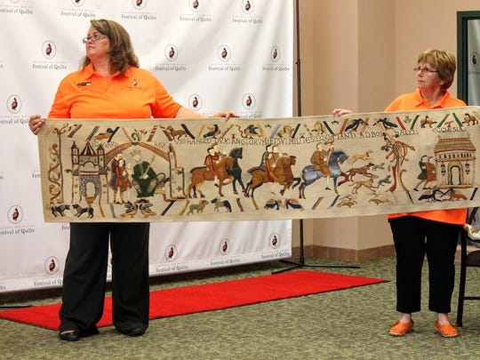 Two festival coordinators hold up a quilt made by Pam Holland Tuesday at First National Bank.