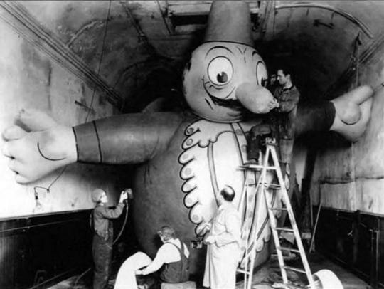 Puppeteer Tony Sarg, in front, touches up one of the balloons for the Macy's Thanksgiving Day Parade.
