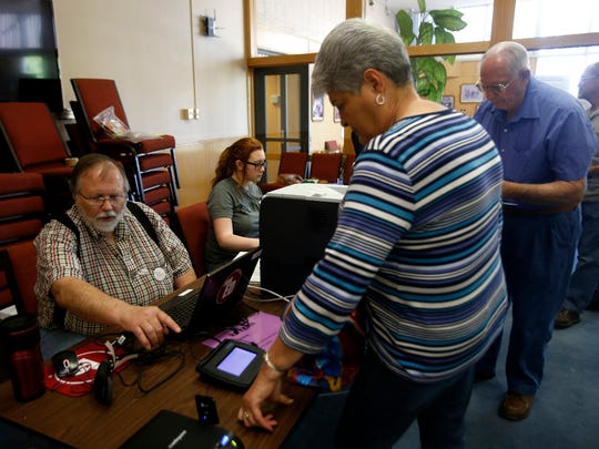 From left, Election workers Mike Wagner, and Olivia Bruce check in voters on Tuesday at Farmington City Hall.