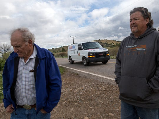 La Plata residents Steve Dunn, left, and Charlie Blassingame talk about the deteriorating condition of the La Plata Highway on Wednesday along the shoulder of the roadway.