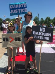 Tayrn Pohl, 8; Sydney Pohl, 6, and their grandmother, Maddie Anderson, all of Ames, held protest signs at an Iowa Capitol rally on June 6, 2016 after the Iowa Utilities Board voted to allow construction to begin on the Bakken pipeline in Iowa.