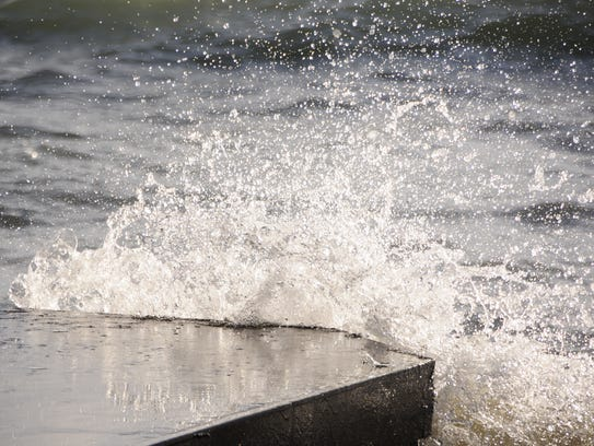 Waves break against a jetty in Lake Huron on Friday,