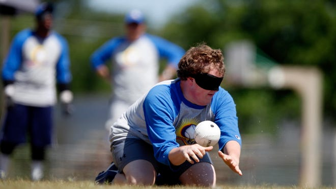 Sam Hogle listens to the beep of the ball as he fields a hit by a player during a blind baseball game in Albany, Ga. on May 5, 2012. Players use their sense of sound to make up for their lack of sight. (AP Photo/David Goldman)