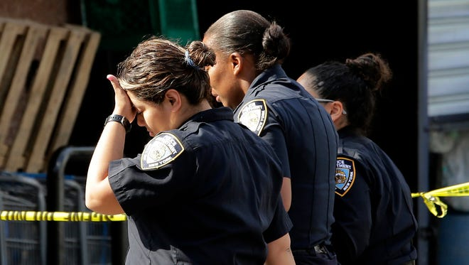Police officers react after visiting the scene where officer Miosotis Familia was fatally shot in the Bronx section of New York, July 5, 2017.