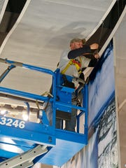 Roy Broeker, of All State Signs, installs 7-by-12-foot photographs at the Great Falls International Airport.