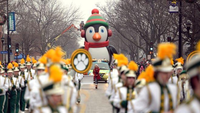 A giant penguin balloon dominates the street as it follows the Ashwaubenon High School band in the 2014 Green Bay Holiday Parade.