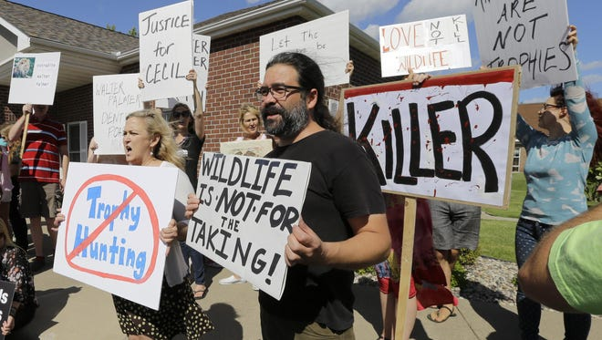 Protestors gather outside Dr. Walter James Palmer's dental office in Bloomington, Minn., on July 29, 2015. Palmer reportedly paid $50,000 to track and kill Cecil, a black-maned lion, just outside Hwange National Park in Zimbabwe.