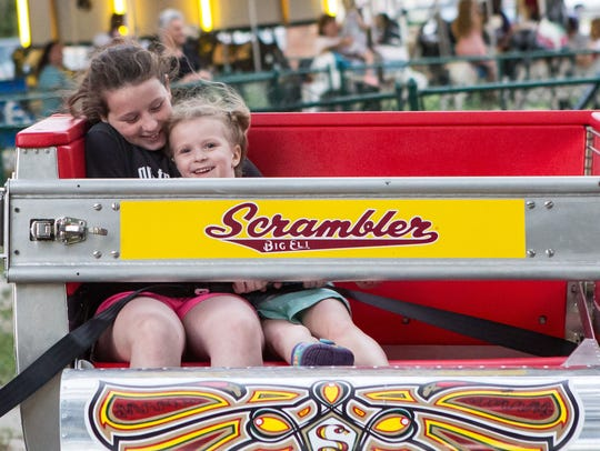 Chloe Bell, 11, and her sister Coral, 4, ride the Scrambler