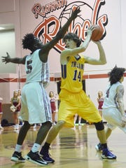 Alexandria Senior High's Connor Grigg (14, right) looks to pass over Pineville's Xavier Gaines (5, left).