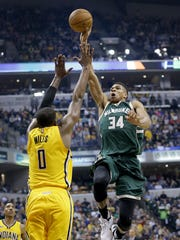 Milwaukee Bucks forward Giannis Antetokounmpo (34) flies through air for a monster dunk overIndiana Pacers forward C.J. Miles (0) in the second half of their game Saturday, February 11, 2017, evening at Bankers Life Fieldhouse. The Indiana Pacers lost to the Milwaukee Bucks 116-100.