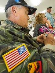 Retired U.S. Army Spc. Freddy Jimenez, of Silver City, New Mexico, looks at a Vietnam veteran lapel pin on Tuesday, March 29, 2016. The pins were distributed at the American Legion Post 10 during the 50th anniversary commemoration of the war for Vietnam veteran clients of the Las Cruces Vet Center.