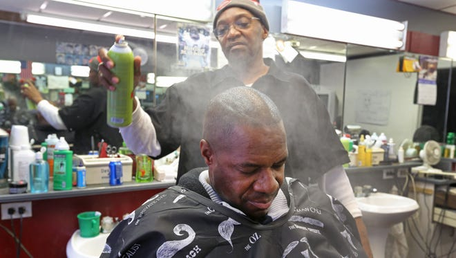Don Johnson has been cutting hair and shaving beards at Haircutters 2 in Over-the-Rhine since 1992. Lorenzo Law, of Anderson, has been making the trek to get his hair tended to every week for the past 20 years.