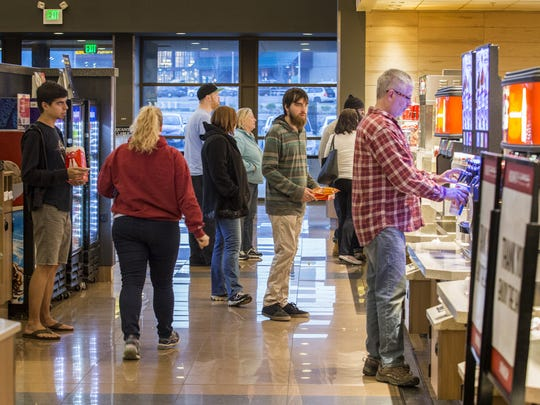 Moviegoers pick up snacks at the self-serve concession stand at Cinemark Christiana earlier this week.