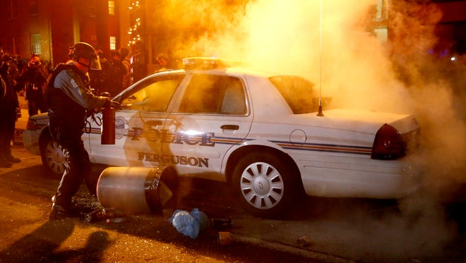 Police officers douse a police car fire after protesters set it ablaze outside City Hall in Ferguson, Mo., on Tuesday.