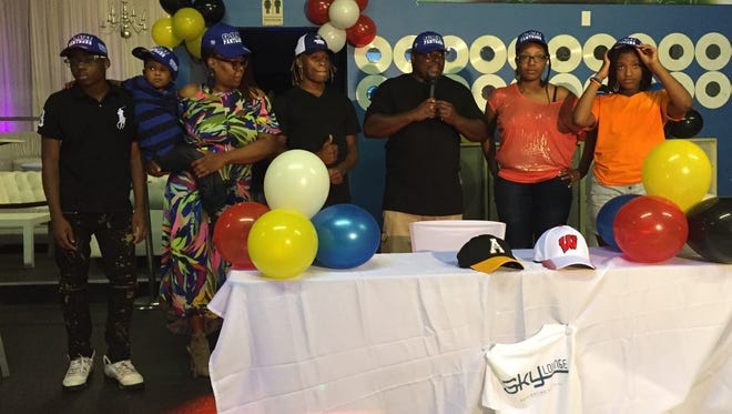 Greer High's Qua White, surrounded by family members, gives a thumbs-up after announcing his commitment to play college football at Georgia State University Saturday at the Sky Lounge in Greenville.