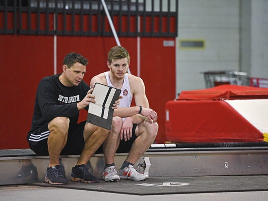 USD pole vaulter Chris Nilsen talks with coach Derek