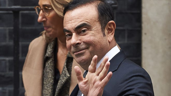 Nissan CEO Carlos Ghosn waves as he leaves No. 10 Downing St. in central London