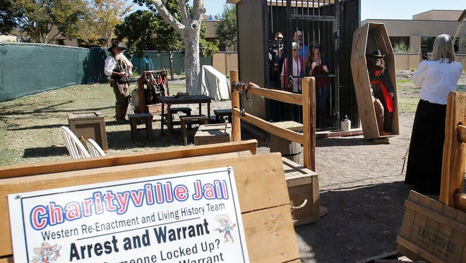 Judy Lightbody, right, owner of the Charityville Jail, takes a photo of Elizabeth Garcia, center left, her husband, Ramon, and their daughter Joanna Moeller and her husband, Chris, and her son Brysen, not visible, at the Tumbleweed Authentic Historical Western Town and Marketplace on Saturday in Simi Valley.