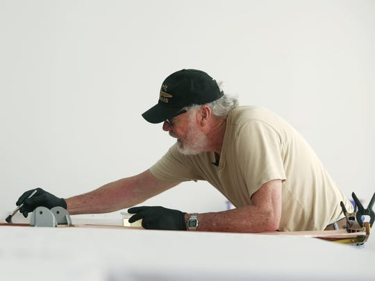 Ken Cassens works on a wing of a Spirit of St. Louis replica at Old Rhinebeck Aerodrome.