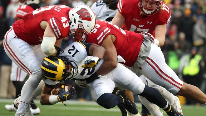 Badgers linebackers Ryan Connelly (left) and T.J. Edwards (right) team up to tackle Michigan running back Chris Evans  for a loss Saturday. The pair combined for 21 tackles in the game against the Wolverines.