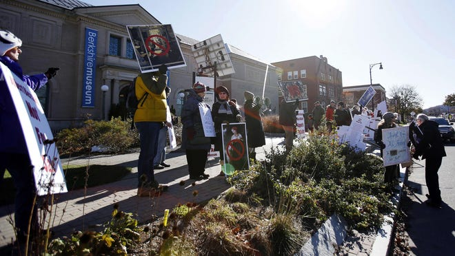 "In this Saturday, Nov. 11, 2017 file photo protestors gather outside the Berkshire Museum, in Pittsfield, Mass., holding signs bearing pleas to ""save the art."" The battle over the proposed sale of dozens of works of art by the museum is scheduled to head to the state's highest court, Tuesday, March 20, 2018. The Berkshire Museum says it needs to sell the 40 pieces of art, including works by Norman Rockwell, to stay open and refocus its mission."