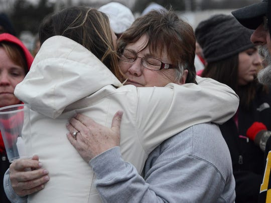 Dozens of community members hugged Beth Fry, whose daughter, son-in-law and two grandchildren died of toxic gas inhalation in Mexico, during a vigil Sunday at the Veterans of Foreign Wars baseball field in Creston.