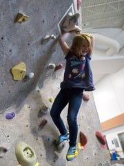 Taryn McGee completes her climbMonday afternoon at the annual Boo-ouldering Competition at the climbing wall at San Juan College Health and Human Performance Center in Farmington.